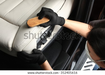 Worker washing of interior by a soft brush with foam. - stock photo