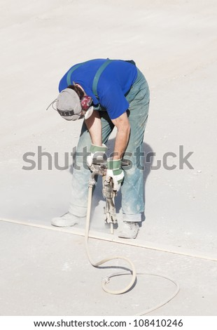 Worker wearing ear and breathing protection using a handheld hydraulic hammer - stock photo