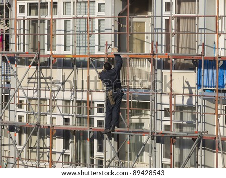 Worker wearing overall and tool belt using hammer to secure a scaffolding tube - stock photo