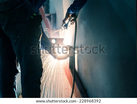 worker weld metal in factory and sparks, filtered images  - stock photo