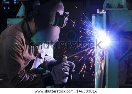 worker welding and bright sparks. metal construction job - stock photo