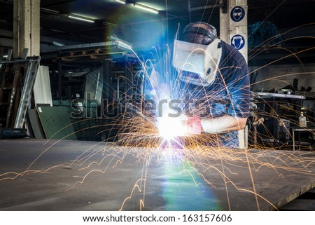 Worker welding in steel workshop with bright light and sparks - stock photo