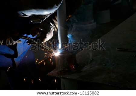 worker welding metal and sparks spreading