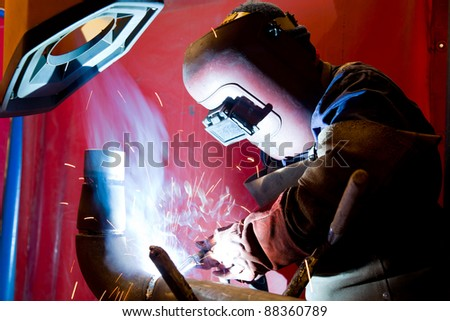 worker welding metal and sparks spreading - stock photo
