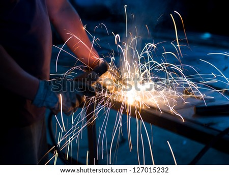 worker welding metal with sparks. - stock photo