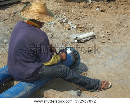 Worker welding steel pipes