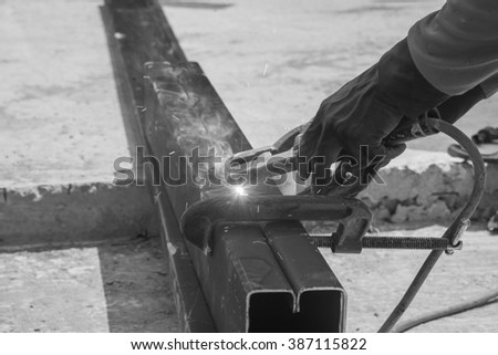 Worker welding steel structure in factory