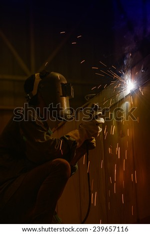 Worker welding the steel part by manual - stock photo