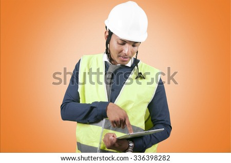 Worker with a tablet on orange background - stock photo