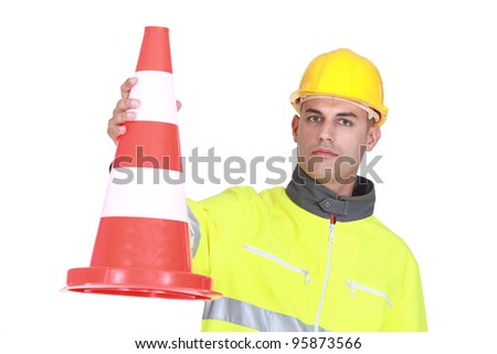 Worker with a traffic cone - stock photo