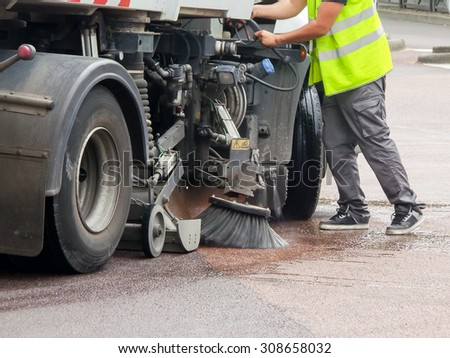 Worker with a truck cleaning a street - stock photo