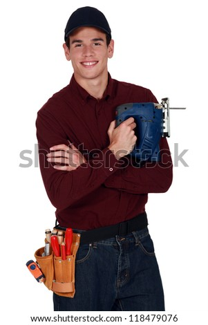 Worker with an electric jigsaw - stock photo