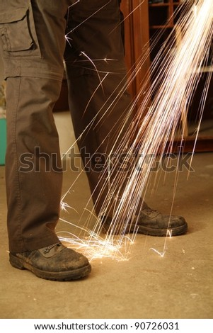 Worker with angle grinder only feet - stock photo