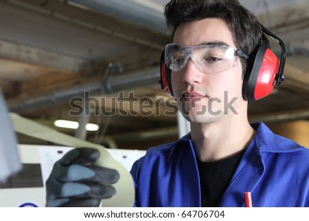 Worker with anti-noise headphones and goggles - stock photo