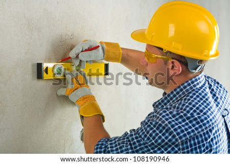 worker with construction level and pencil