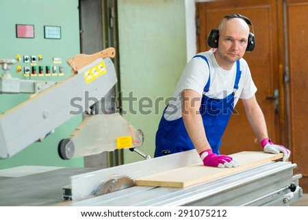 worker with ear protector in a carpenter's workshop