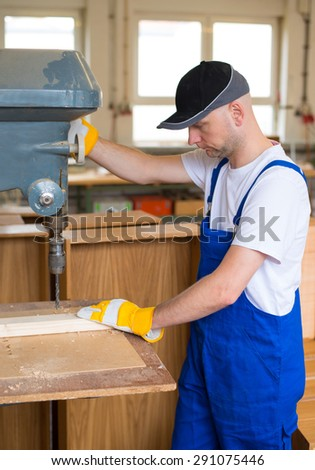 worker with ear protector in a carpenter's workshop - stock photo