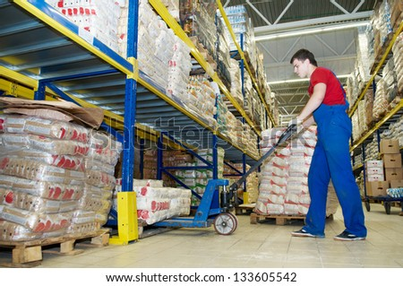 worker with fork pallet truck stacker in warehouse loading Group of food packages - stock photo