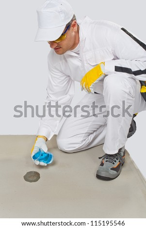 Worker with glass flask of water testing the humidity of cement
