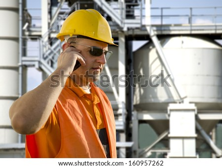 worker with helmet and sunglasses talking on mobile phone in front of oil plant - stock photo