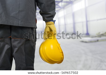worker with helmet in production hall - stock photo
