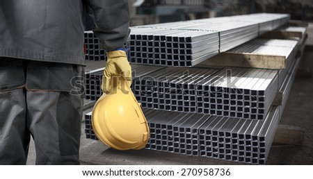 worker with helmet in production hall in front of steel sheet metal profiles  - stock photo