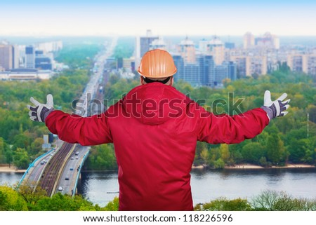 Worker with his arms raised on a cityscape background - stock photo
