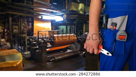 Worker with instruments at industrial factory - stock photo