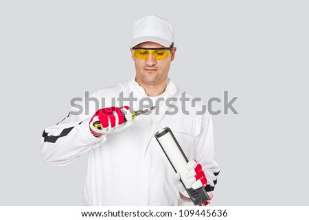 Worker with knife remove cuts cap sealant silicon gun - stock photo