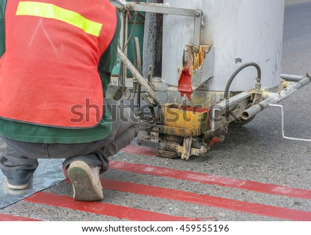Worker with machine at road construction