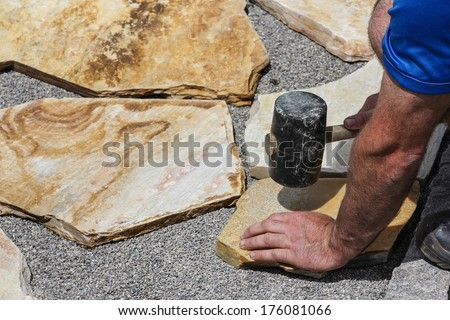 Worker with marble plates and hammer - stock photo