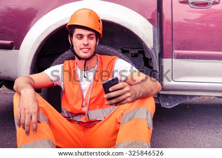 Worker with mobile phone and helmet relaxing outdoors - Workman with safety clothes and hardhat having fun surprised facial expression by sharing sms - Concept of communication available to everyone - stock photo