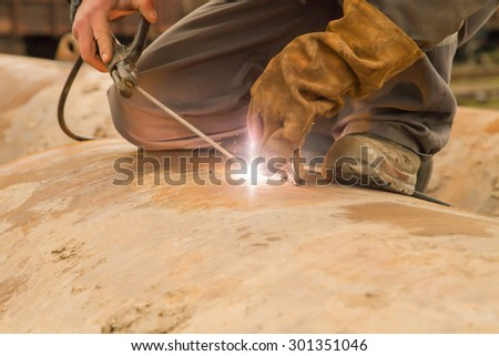 Worker with protective clothing and masks weld metal with electrocautery - stock photo