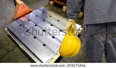 worker with protective helmet and protective gloves in front of tin metal