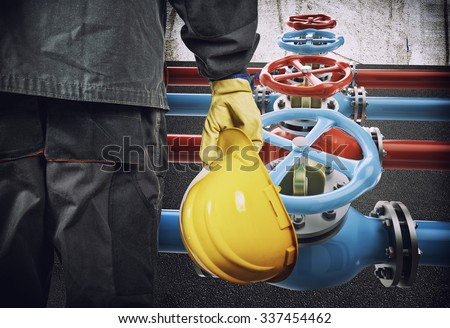 worker with protective helmet in front of industrial refinery oil pipes with valves - stock photo