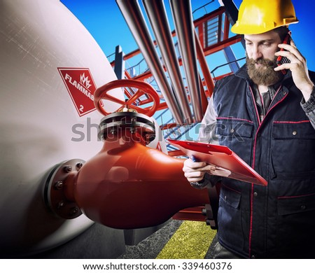 worker with protective helmet in front of industrial refinery tanks and pipes with valves - stock photo