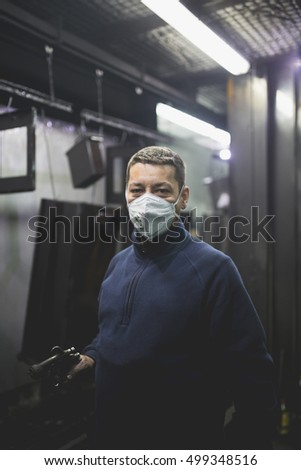 Worker with protective mask in factory for production heavy pellet stoves and boilers.