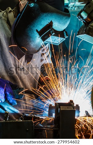 worker with protective mask welding metal - stock photo