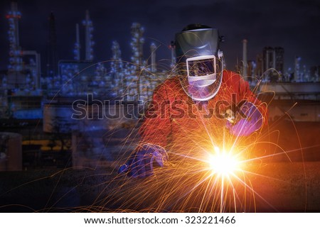 worker with protective mask welding metal and sparks in oil refinary plant. - stock photo