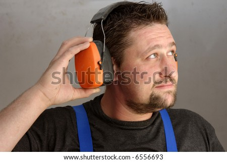 Worker with protective soundproofing ear muffs on - stock photo