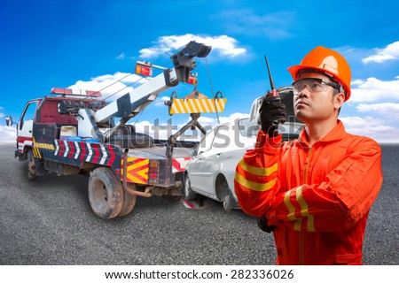 Worker with radio communication in action for working at heavy duty truck used for towing accident saloon car on the road - stock photo