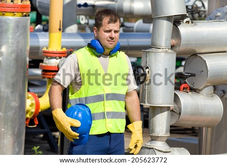 Worker with safety equipment on oil plant - stock photo