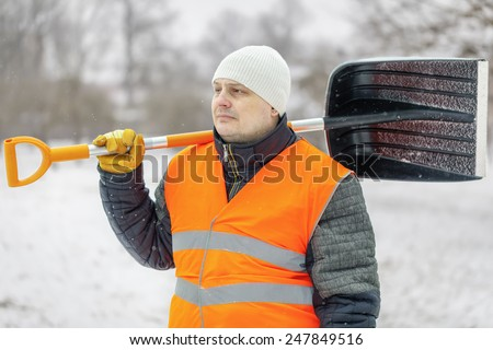 Worker with snow shovel in winter - stock photo