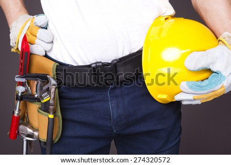 Worker with toolbelt and helmet against dark background - stock photo
