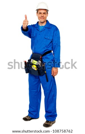 Worker with tools bag showing thumbs up standing against white background - stock photo