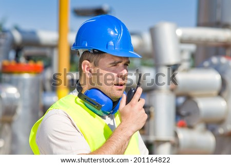Worker with walkie talkie and safety equipment on oil plant - stock photo
