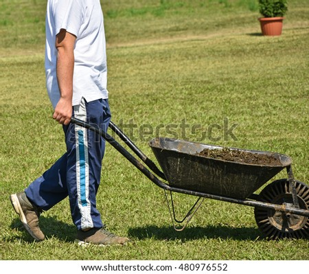 Worker with wheelbarrow full of manure