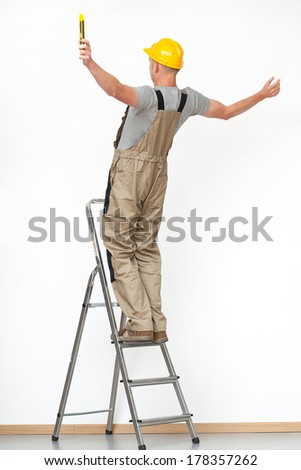 Worker with yellow helmet  falling from aluminium ladder  - stock photo