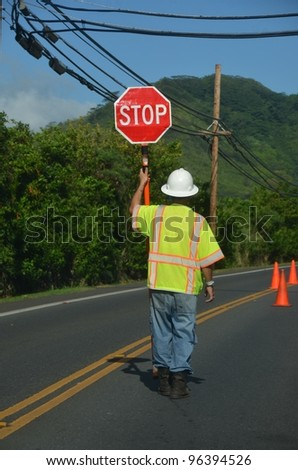 worker with yellow west holds stop sign - stock photo
