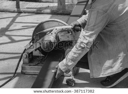Worker working on cutting a metal and steel with compound mitre saw with sharp, circular blade - stock photo